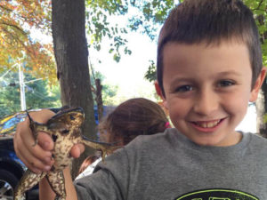 young boy holding frog