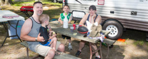 family sitting at picnic table on campsite