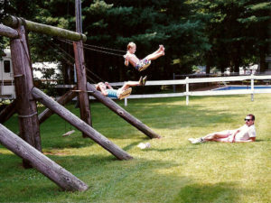 old photo of young boys swinging at playground with dad watching