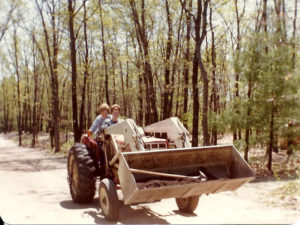old photo of two people on tractor