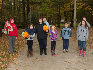 campers holding pumpkins at halloween